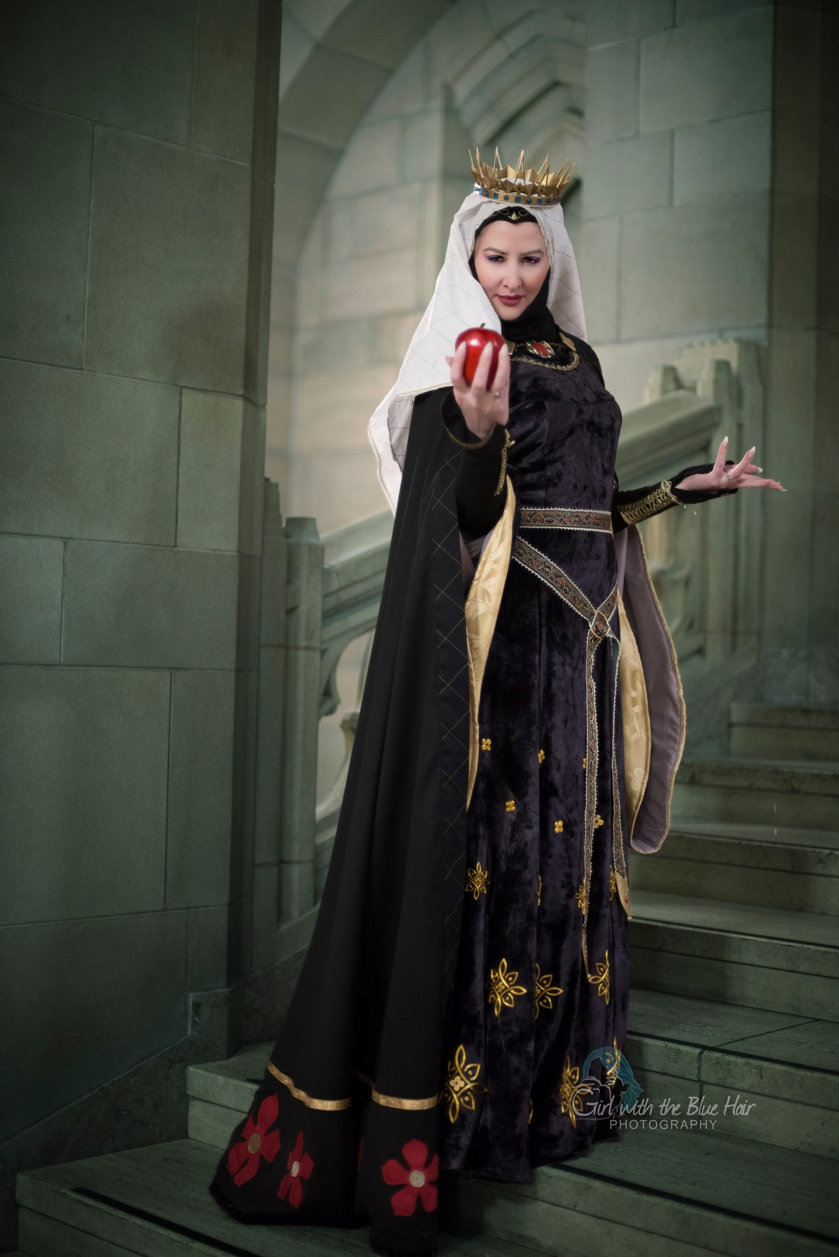 Medieval Evil Queen stands on a staircase holding up a red apple to the viewer.